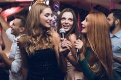 三个美丽的女孩在卡拉OK演唱俱乐部唱歌 在他们后是等待他们的轮的人 库存图片