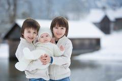 三个美丽的男孩,兄弟,有在冬天sunn的画象 库存照片