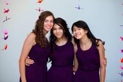 三个美丽的青少年的女孩在配比的pruple一起穿戴 库存照片