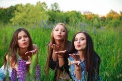 三个美丽的年轻愉快的女孩最好的朋友送有空气的亲吻乐趣,微笑和笑 湿背景概念黑暗的友谊鹈鹕的纵向二 库存图片