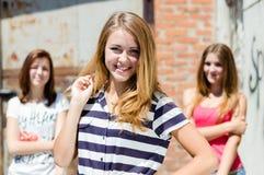 三个美丽的年轻愉快的女朋友获得乐趣在城市户外 免版税图库摄影