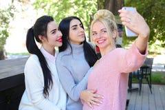 三个美妙的女孩女朋友做selfie,在pho的照片 库存图片