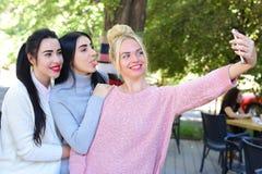 三个美妙的女孩女朋友做selfie,在pho的照片 免版税库存图片