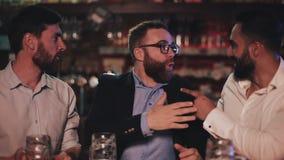 三个老朋友喝桶装啤酒和谈话在娱乐酒吧 笑的朋友和在啤酒客栈谈论新闻 影视素材