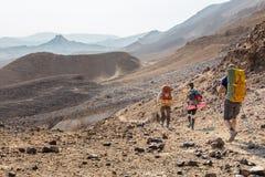 三个背包徒步旅行者走的石沙漠足迹 免版税库存图片