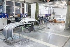 三个自动防撞器零件在机架被安装在绘以后在汽车维修车间在有工具和设备的屋子里 免版税图库摄影