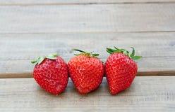 三个草莓在木地板上关闭  免版税库存照片