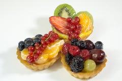 三个蛋糕用新鲜的生物果子,桔子,猕猴桃,草莓,蓝莓,红浆果,葡萄,莓,黑莓,边 免版税图库摄影