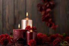 三个蜡烛在黑暗的背景机智的绯红色和桃红色颜色 图库摄影
