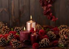 三个蜡烛在黑暗的背景机智的绯红色和桃红色颜色 库存照片
