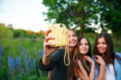 三个行家女孩金发碧眼的女人和深色的采取的自画象在偏振光相机和微笑室外 获得的女孩乐趣一起 库存照片