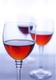 三个透明葡萄酒杯用玫瑰酒红色。 库存照片