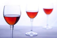三个透明葡萄酒杯用玫瑰酒红色。 免版税图库摄影
