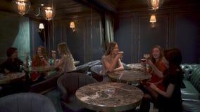 三个逗人喜爱的女孩在咖啡馆坐或餐馆有一晚上好和是叮当声的玻璃微笑和在心情 股票视频