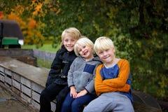 三个逗人喜爱的孩子被包的拖拉机无盖货车乘驾在冷颤的秋天天 免版税库存照片