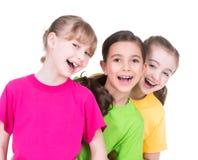 三个逗人喜爱的矮小的逗人喜爱的微笑的女孩。 免版税图库摄影