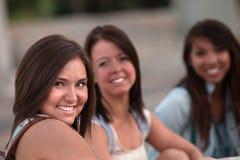 三个逗人喜爱青少年女孩坐 免版税库存图片