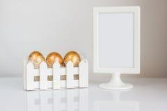 三个金黄复活节彩蛋和典雅的照片框架在白色背景 图库摄影