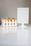 三个金黄复活节彩蛋和典雅的照片框架在白色背景 库存照片
