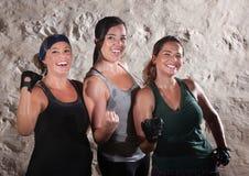 三个锻炼夫人屈曲他们的二头肌 免版税库存照片