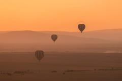 三个镶边的气球飞行在紫色小山 免版税库存照片