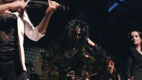 三个阶段的了不起的女孩小提琴手 凉快的摇滚乐队 女孩非常情感地和传神使用 股票视频