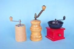 三个香料在蓝色背景的胡椒研磨机 库存照片