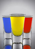 三个鸡尾酒染黄在三酒gla的红色和蓝色颜色 免版税图库摄影