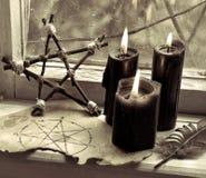 三个黑蜡烛、页与五角星形和木五角星形由老窗口 免版税图库摄影