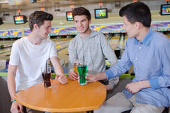 三个年轻人在保龄球场的havng饮料 库存照片