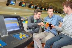 三个年轻人在保龄球场的havng饮料 免版税库存图片