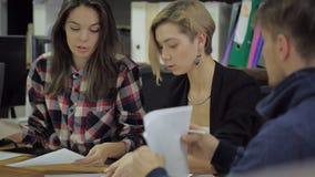 三个年轻人在谈论的桌上被描述的某事坐纸片 股票录像