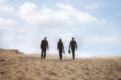 三个年轻商人走通过沙漠的,背面图,遥远 图库摄影