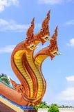 三个头在楼梯的龙雕象在有蓝天的寺庙 免版税库存照片