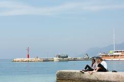 三个年轻少年坐亚得里亚海和谈话的岸 库存图片