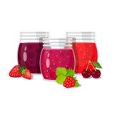 三个玻璃瓶子果酱用莓果 免版税库存照片