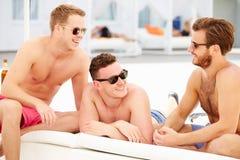 三个年轻男性朋友在度假由一起水池的 免版税库存图片