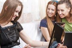 三个年轻白种人女朋友画象有膝上型计算机的Looki 免版税图库摄影