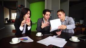 三个负责任的银行家、人和女朋友与文献和小配件一起使用,在办公室沟通并且坐  影视素材