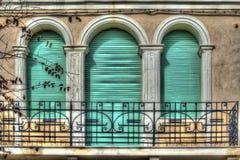 三个绿色路辗窗帘在一个老意大利阳台上 免版税库存照片