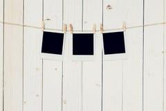 三个3blank垂悬在白色木背景的照片框架与 免版税库存照片