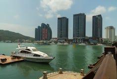 三亚河的堤防的现代摩天大楼在海南岛上的三亚市 免版税库存照片