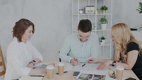 三位创造性的设计专家在工作流介入 美丽的白肤金发的妇女与a姿势示意并且讲话 股票录像