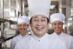 三位厨师在一个工业厨房里 库存图片