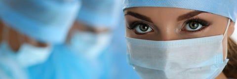 三位外科医生在运行在外科剧院的工作 免版税库存图片
