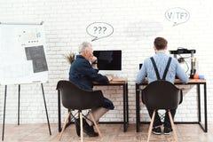 三位工程师与一台3d打印机一起使用在一个现代实验室 他们有在他们的头的会话云彩 库存照片