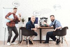 三位工程师与一台3d打印机一起使用在一个现代实验室 他们有在他们的头的会话云彩 免版税库存照片