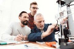 三位工程师在3d打印机打印细节 一个老人人控制过程 两其他跟随过程 免版税库存照片