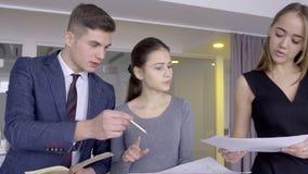 三位年轻建筑师在他们的现代演播室谈论项目 股票录像