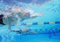 三位男性运动员水下的射击在游泳竞争中 免版税图库摄影